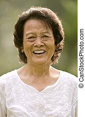 Ältere Asiatin lächelt.