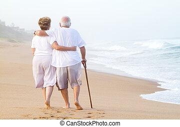 Älteres Paar, das am Strand spazieren geht.