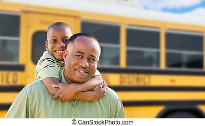 Afrikanischer amerikanischer Mann und Kind Huckepack in der Nähe des Schulbusses.