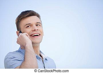 Am Telefon. Ein fröhlicher junger Mann, der am Handy redet und lächelt