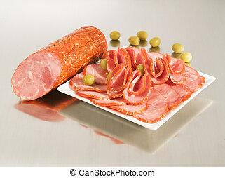 Arrangement mit frischer Dry Krakow Sausage auf einem Stahlsilberbrett mit Oliven.