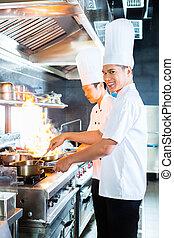 Asiatische Köche kochen im Restaurant.
