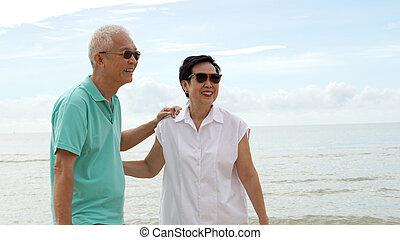 Asiatische Senioren, die am Strand am Meer zusammenlaufen.
