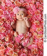 Baby in einem Bett voller Rosen