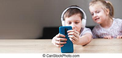 banner, headphones., smartphone, zwei kinder, leute, concept., spielende , glücklich, technologie