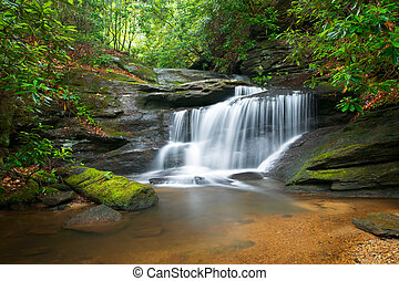 Bewegung verschwommene Wasserfälle, friedliche Naturlandschaft in den blauen Bergkammbergen mit üppigen grünen Bäumen, Felsen und fließendem Wasser