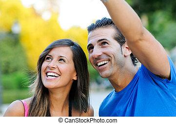 Bild von einem glücklichen jungen Paar, das sich etwas Interessantes anschaut