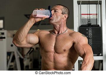 Bodybuilder mit Protein-Shaker.