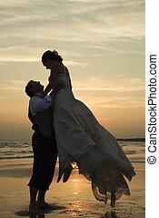 Bräutigam hebt Braut hoch.