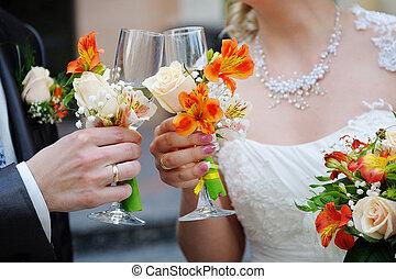 Braut und Bräutigam haben Champagnergläser.