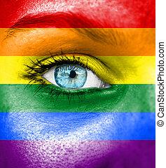 Das Gesicht der Frau mit der Flagge von Pride gemalt.