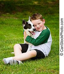 Das Kind umarmt liebevoll seinen Schoßhund