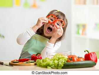 Das Mädchen hat Spaß mit Gemüse.