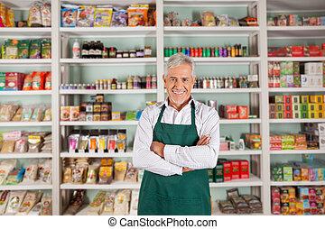Der ältere Besitzer steht im Supermarkt