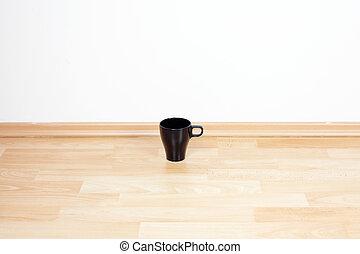 Der Becher steht auf dem Boden im Zimmer.