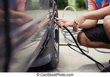 Der Fahrer kontrolliert Luftdruck und füllt die Reifen.
