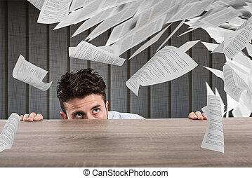Der Geschäftsmann fürchtet sich unter dem Schreibtisch. Konzept der Überarbeitung