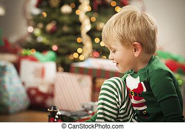 Der Junge genießt den Weihnachtsmorgen in der Nähe des Baumes