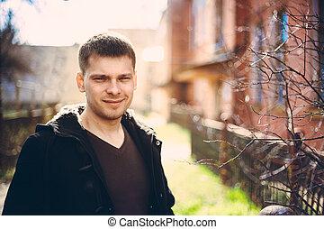 Der junge, gutaussehende Mann wohnt im Herbst in der Nähe des alten Holzhauses