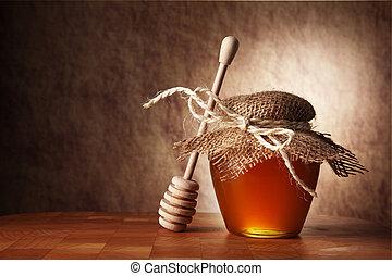 Der Topf mit Honig und Holzstock ist auf einem Tisch.