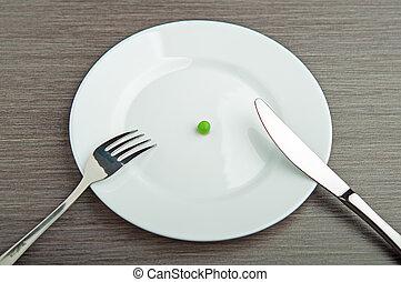 Diät-Konzept. Eine Erbse auf einem leeren weißen Teller