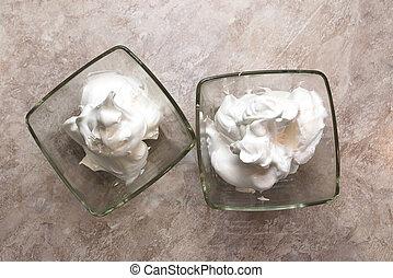 Die Creme-Meringues in einem Glasbehälter.