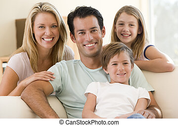 Die Familie sitzt im Wohnzimmer und lächelt.