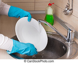 Die Frau wäscht Geschirr im Waschbecken.