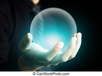 Die Hand hält eine leuchtende Kristallkugel