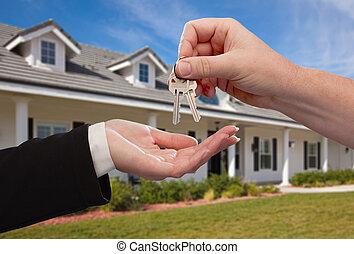 Die Hausschlüssel vor dem neuen Zuhause übergeben