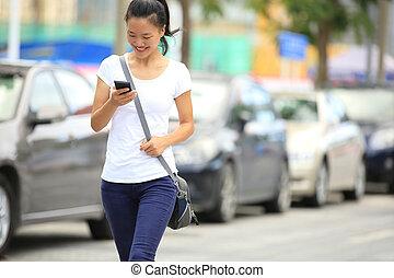 Die junge Asiatin benutzt ihr Handy.