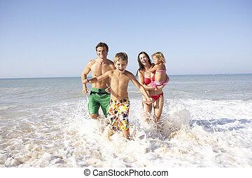Die junge Familie spielt am Strand.