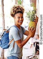Die lachende Schwarze steht draußen mit Ananas.