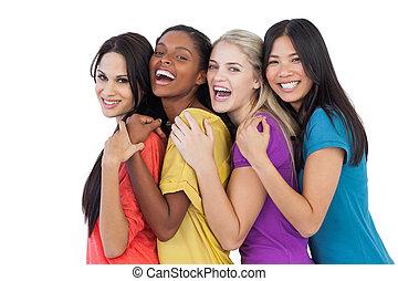 Diverse junge Frauen lachen über Kamera und Umgebung.