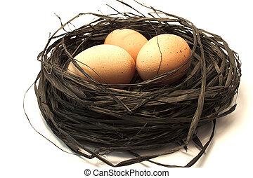 Drei braune Eier in einem Nest.