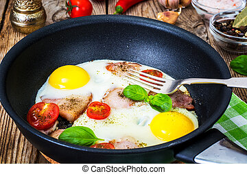 Eier mit Speck und Tomaten in einer Pfanne