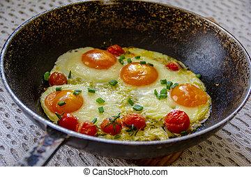 Eier mit Tomaten in einer Pfanne.