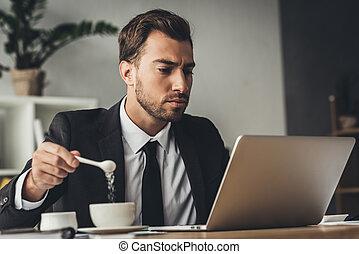 Ein Geschäftsmann, der Zucker zum Kaffee macht.