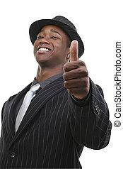 Ein Geschäftsmann im Anzug und Hut, der die Daumen hochstreckt