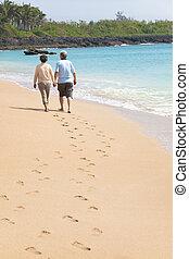 Ein glücklicher Senior, der mit Fußabdrücken am Strand spazieren geht
