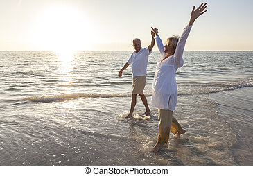 Ein glückliches, älteres Paar, das Händchen hält, Sonnenuntergangs Strand