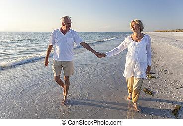 Ein glückliches älteres Paar, das Händchen hält, tropischer Strand