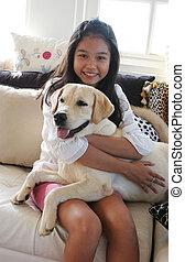 Ein glückliches asiatisches Mädchen mit ihrem Schoßhund