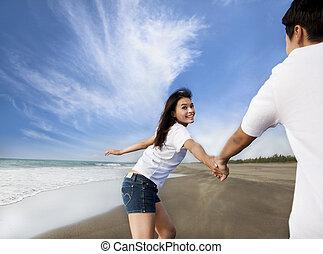 Ein glückliches asiatisches Paar, das am Strand rennt