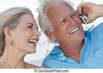 Ein glückliches Paar, das über Handy redet