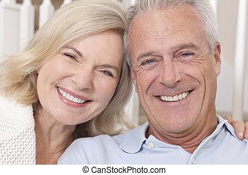Ein glückliches Senior-Man-Frauenpaar, das zu Hause lächelt