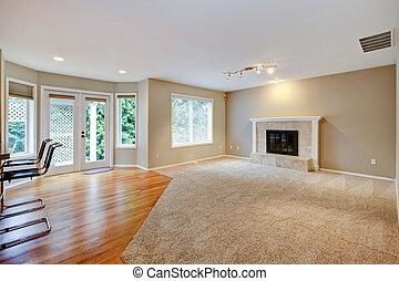 Ein großes, helles, leeres Wohnzimmer mit Kamin.