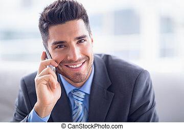 Ein gut aussehender Geschäftsmann, der auf dem Sofa sitzt und einen Anruf macht, der bei der Kamera im Büro lächelt.