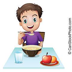 Ein Junge, der sein Frühstück am Tisch isst.