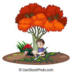 Ein Junge, der unter dem Baum liest.